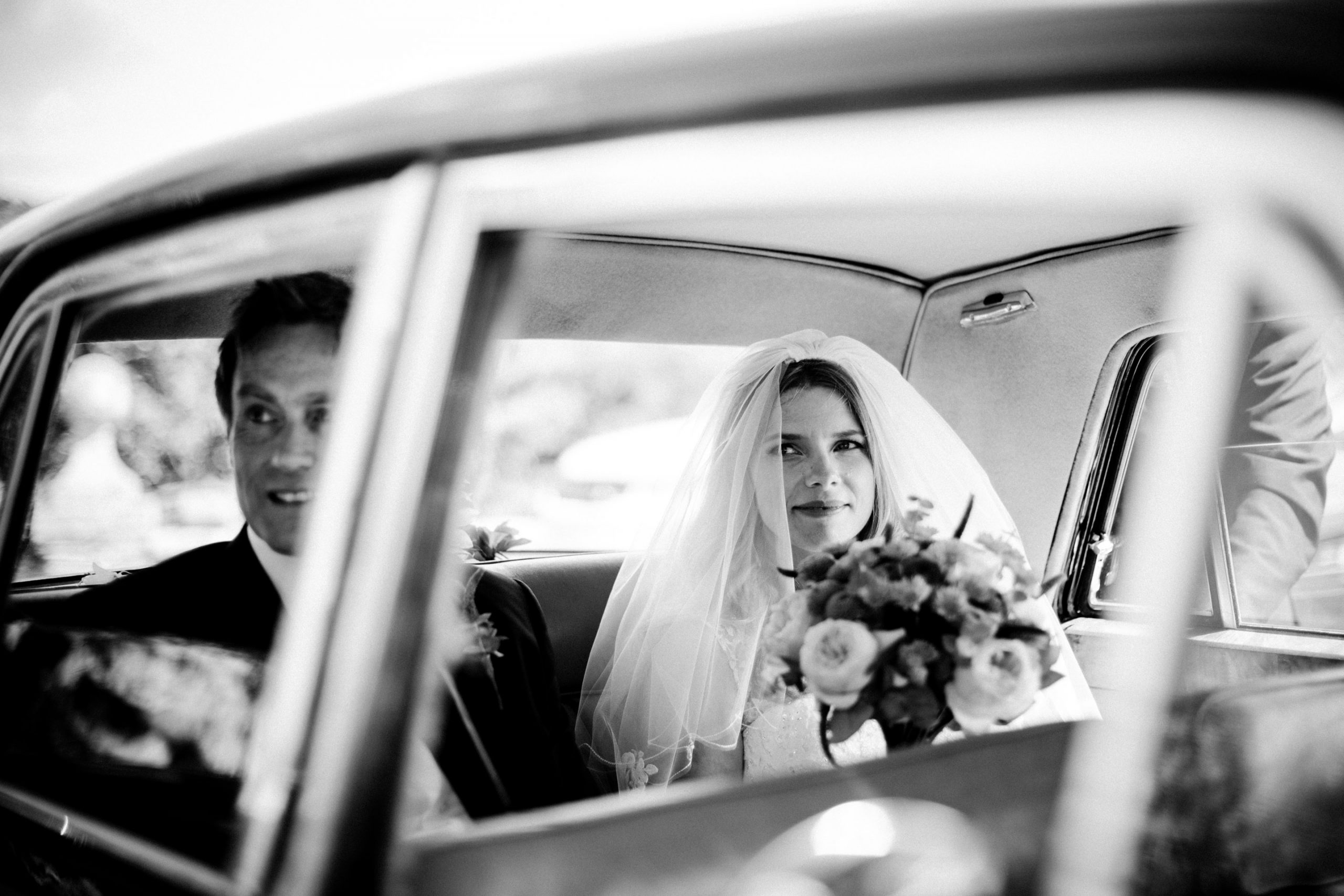 Helen & Kevin are seen through the window of their wedding car on their way from their Wembury wedding at St Werburgh's Church to their reception at the Langdon Court Hotel in Devon.