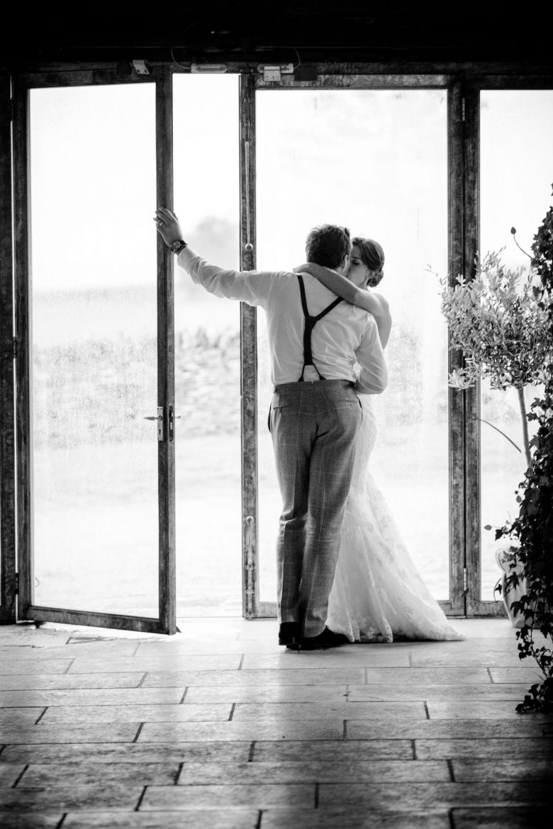 A bride and groom share an unposed kiss by the entrance to Cripps Stone Barn